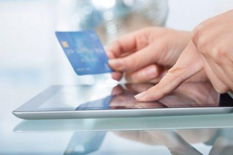 Pagamentos Digitais - Mãos segurando um cartão de crédito sobre um tablet